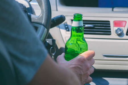 Man holding green bottle of beer in hand while driving a car. Don't drink and drive concept Imagens