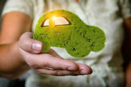 Concept of eco friendly, think green and other ecological ideas. Green car with grass growing on it floating over woman's hand
