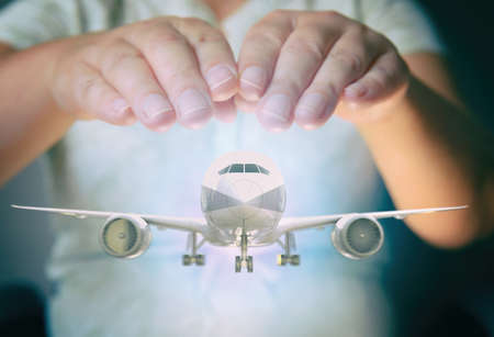 A plane airliner under woman's hands in a protective position. Aircraft industry concepts, airline safety and insurance