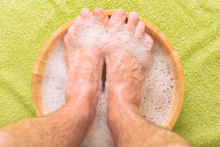 Male feet in a bowl with water and soap, hygiene and spa concept Imagens