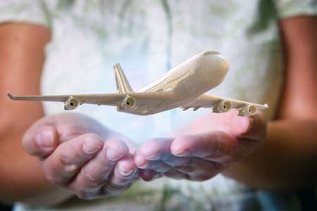 A plane airliner over woman's hands in a protective position. Aircraft industry concepts, airline safety and insurance