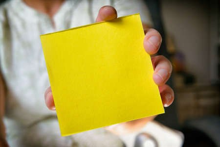 Woman showing a blank yellow sticky note paper. Empty space for your text. Imagens