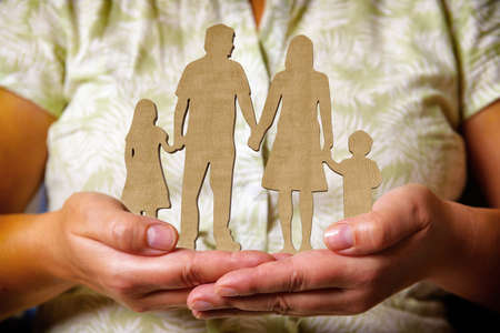 Wooden figures - family, children and parents in a line holding hands and standing in the hands of a woman