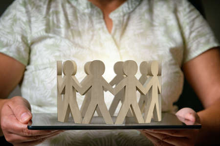Wooden figures of people in a circle holding hands and standing on the tablet. The concept of a social network, business or other relationships. Setting the men on the tablet suggests connection via the internet network.