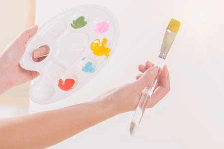 Hands of woman artist holding palette with different paints and paintbrush in a workshop studio.