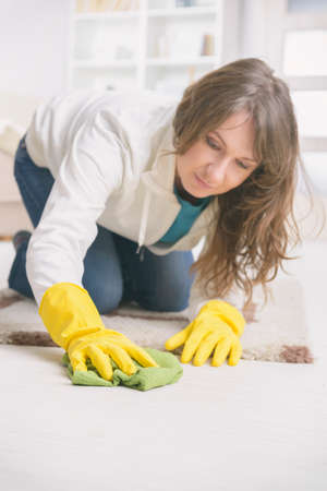 Smiling woman in yellow rubber gloves wiping dust on floor at home