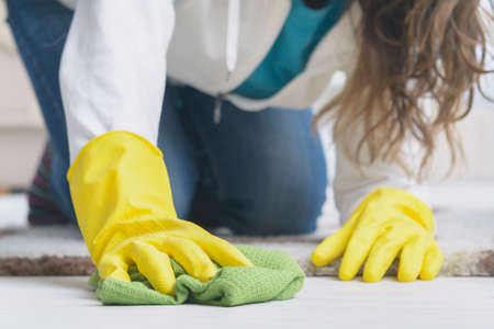 woman in yellow rubber gloves wiping dust on floor at home