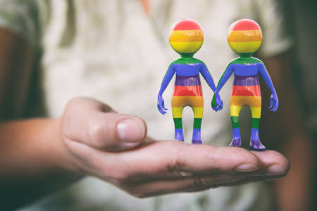 Couple holding hands, a rainbow flag symbol of the LGBT community, equal rights for lesbian, gay, bisexual, transgender minorities. Imagens