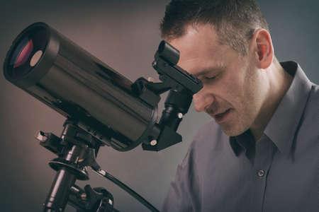 Man looking skyward through astronomical telescope Imagens