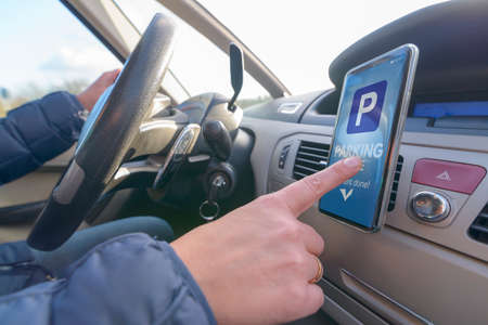 Woman using smartphone app to pay for parking in the paid parking zone in a city