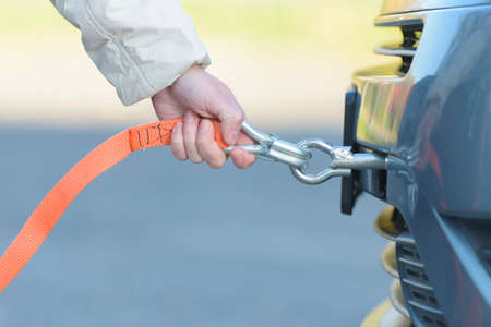 Woman assembling towing line to a broken car Stock Photo