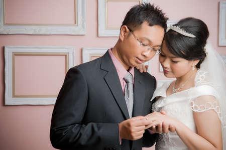 ポーズの結婚式で新郎新婦ドレスアップ スタジオでは、笑みを浮かべて