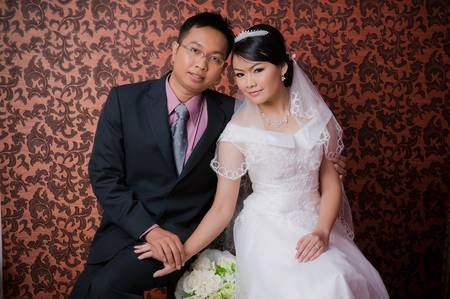 Bride and Groom posing in wedding dress at studio, smiling photo