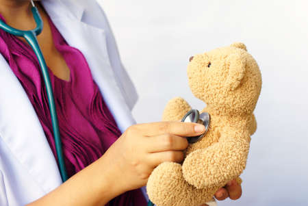 doctor, using a stethoscope with doll photo