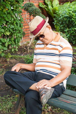 old man nap on a bench in the garden photo