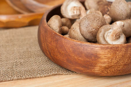 Fresh mushrooms in bowl on wooden background photo
