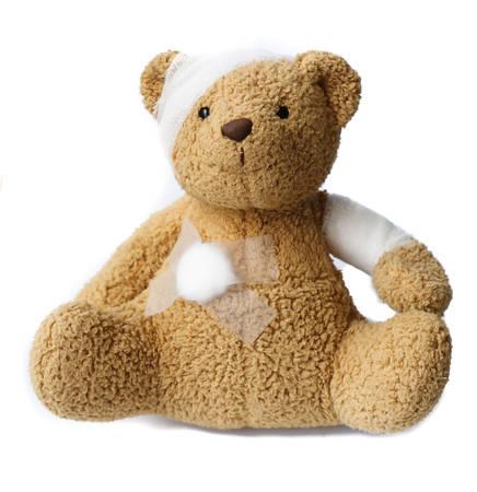 teddy bear with bandaged head on white background photo