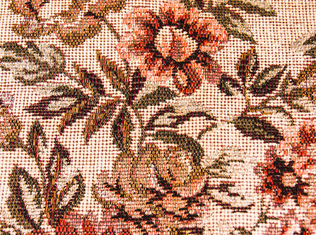 Fragment of retro tapestry fabric pattern with colorful floral ornament on white  photo