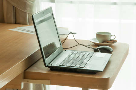 Close up view of a work desk interior with a laptop computer, a cup of coffee and white curtains photo