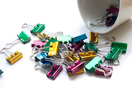 Heap of binder clips isolated on white photo