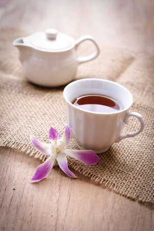 cup of black coffee  with purple orchid and burlap cloth on wooden table photo