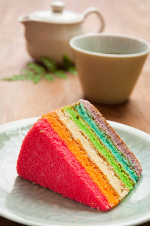 Delicious rainbow cake on plate on table photo