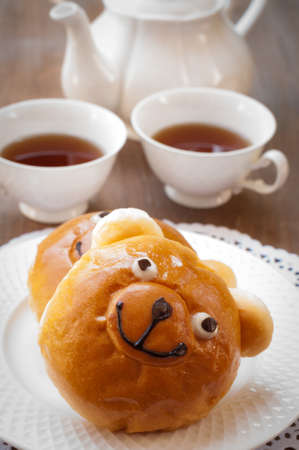 sweet bun: Sweet bun and cup of tea on wooden table