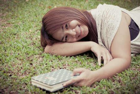 beautiful asian woman reading a book in the garden photo