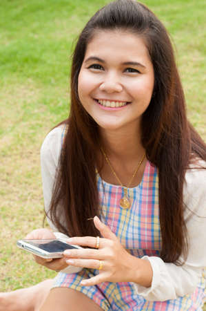 Modern teenager girl using a smart phone in a park with a green  photo