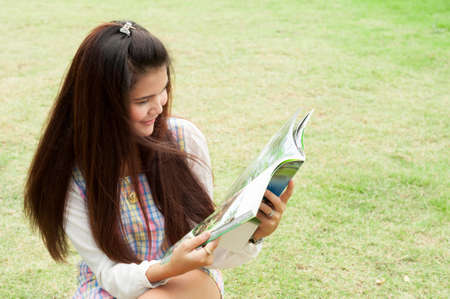 Happy woman reading a magazine in a park with a green  photo