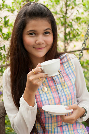 A shot of a beautiful asian woman drinking coffee in the garden photo