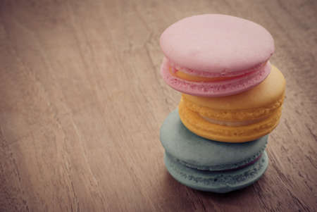 colourful stack flavoured macaron on white wood background photo