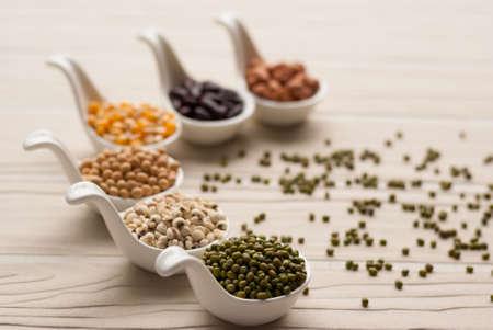 macrobiotic: Different kinds of bean seeds, lentil, peas in dish on wooden table, macrobiotic food or healthy food