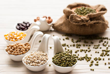 protein crops: collection set of beans, legumes, peas, lentils on ceramic spoons on white wooden background Stock Photo