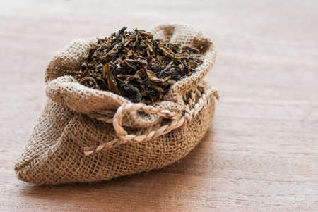 dried tea leaves in burlap sac on wooden background Stock Photo
