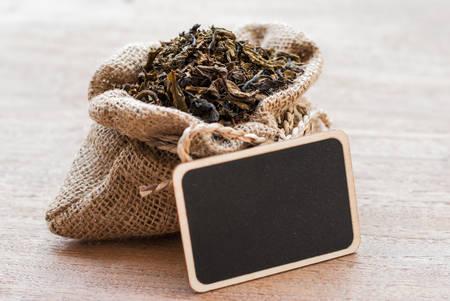burlap sac: dried tea leaves in burlap sac on wooden background Stock Photo