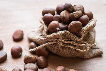 burlap sac: Chestnuts in burlap sac on wooden board Stock Photo