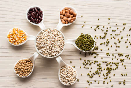 collection set of beans, legumes, peas, lentils on ceramic spoons on white wooden background photo