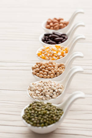 macrobiotic: Different kinds of bean seeds, lentil, peas in dish on wooden table, macrobiotic food or healthy food