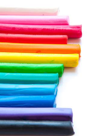 clay modeling: Rainbow colors plasticine play dough modeling clay isolated over white. Stock Photo