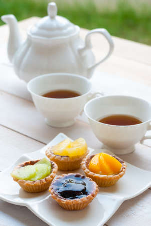 short crust pastry: Fruit tart with tea on wooden board afternoon tea
