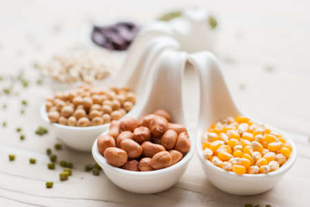 Different kinds of bean seeds lentil peas in dish on wooden table macrobiotic food or healthy food photo