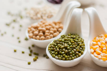 Different kinds of bean seeds lentil peas in dish on wooden table macrobiotic food or healthy food Archivio Fotografico