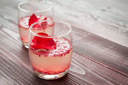 sparkling wine: Pink Cocktail with fresh rose petals on wooden table Stock Photo