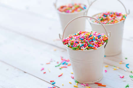 chocolate balls: Sugar sprinkle dots, decoration for cake and bekery, a lot of sprinkles in a bucket on white wooden board background Stock Photo
