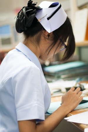 nurse station: Nurse Using Mobile Phone At Nurses Station Stock Photo
