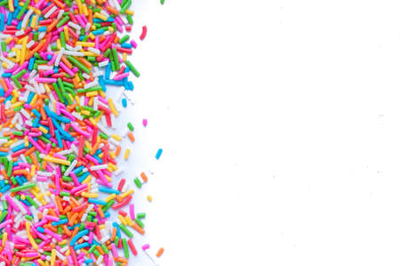 white sugar: Sugar sprinkle dots, decoration for cake and bekery, a lot of sprinkles in a bucket on white wooden board background Stock Photo