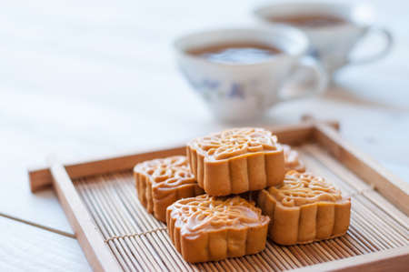 mid: Retro vintage style Chinese mid autumn festival foods. Traditional mooncakes on table setting with teacup.