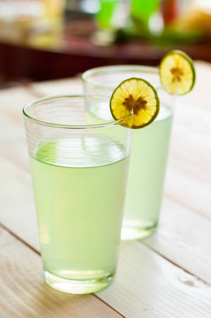 icecubes: Cold lemonade in a glass, served with a slice of a lemon