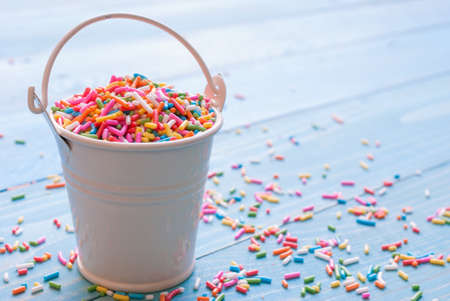 blue balls: Sugar sprinkle dots, decoration for cake and bekery, a lot of sprinkles in a bucket on white wooden board background Stock Photo